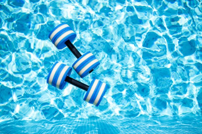 Top view of plastic dumbbells for aqua aerobics floating in blue water of swimming pool on summer day outdoors