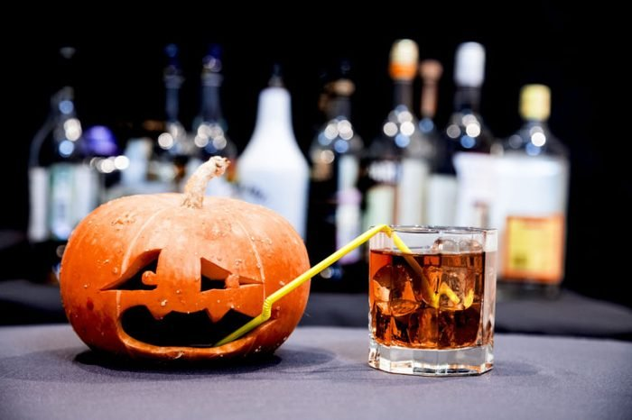 Halloween party. Funny Pumpkin with a cocktail