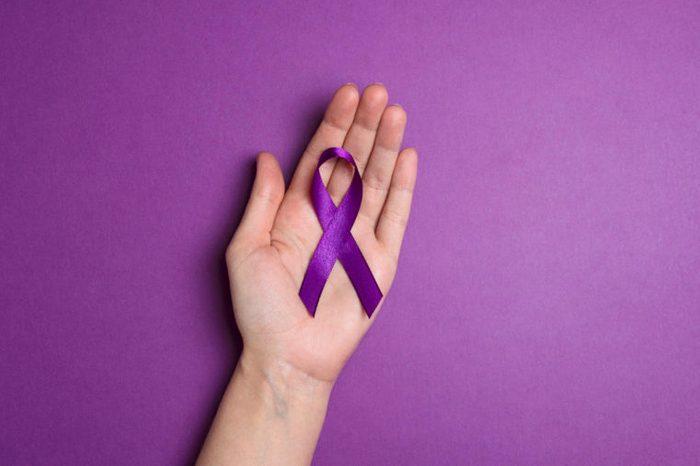 Hand holding Purple ribbons on a p urple background. World epilepsy day. Alzheimer's disease, Pancreatic cancer, Epilepsy awareness, fibromyalgia awareness.