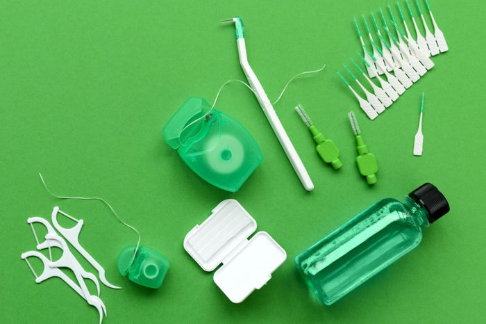 Different tools for dental care on green background. Toothbrush, cleanser, floss, flossers, wax for braces and interdental brush. Top view. Flat lay. Dental hygiene and care concept