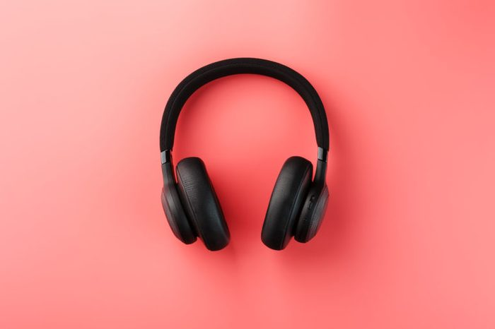 Wireless black headphones on a pink background. On-ear headphones for playing games and listening to music tracks.