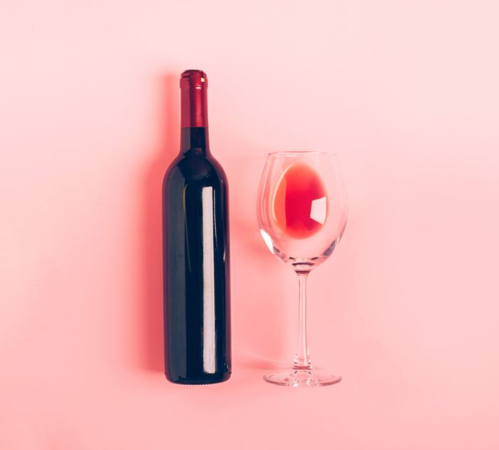 A bottle of wine an empty glass of a bunch of red grapes on a gentle pink background. Flat layout top view. Copy space. Minimalism. Horizontal frame; Shutterstock ID 1409701445; Job (TFH, TOH, RD, BNB, CWM, CM): -