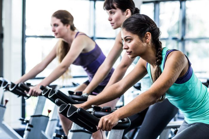 woman working out exercise bike class gym diverse asian
