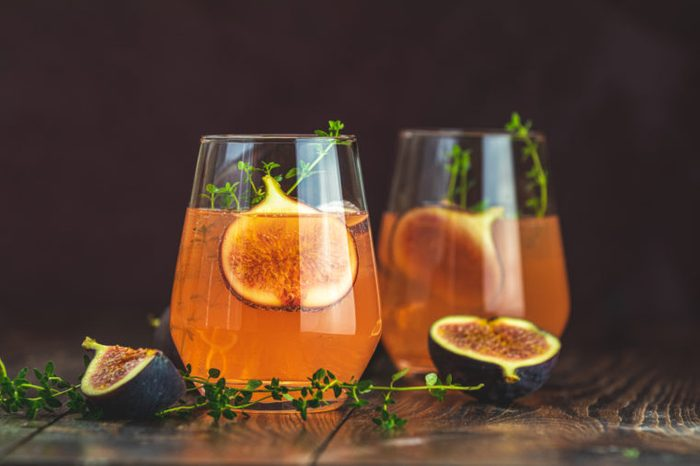 Pink cocktail with fig, thyme and ice in glass on dark wooden background, close up. Summer drinks and alcoholic cocktails. Alcoholic or detox cocktail