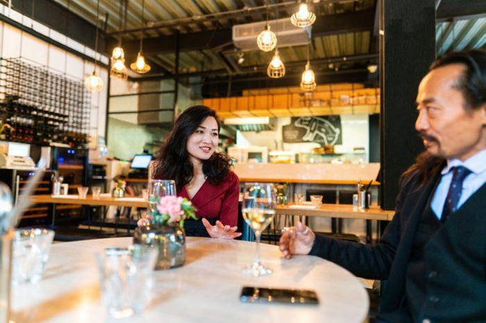 man and woman talking at dinner