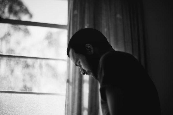 man thinking in bedroom