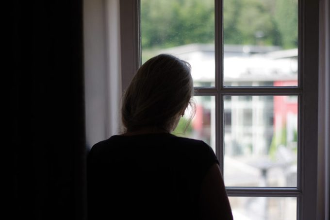 woman silhouette looking out of window of home