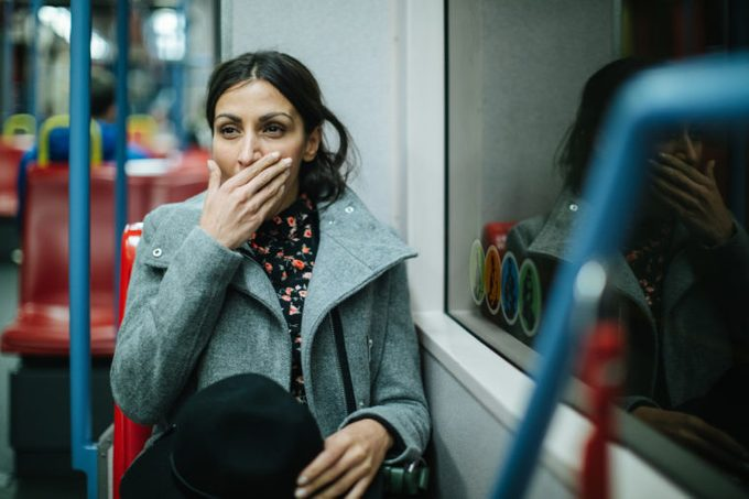 exhausted woman sitting on public transit after a long day