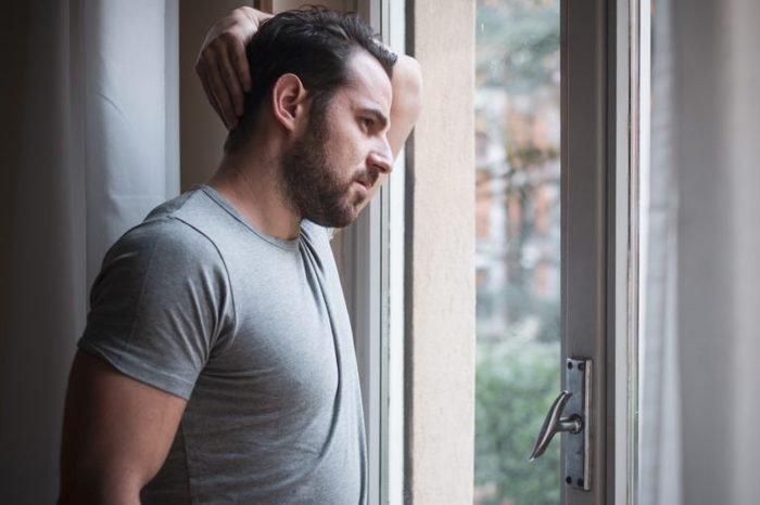 man looking out of window of home