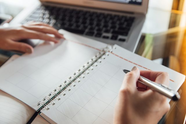 Writing in a datebook with a pen