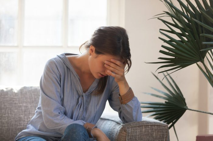 fatigued woman sitting on couch at home