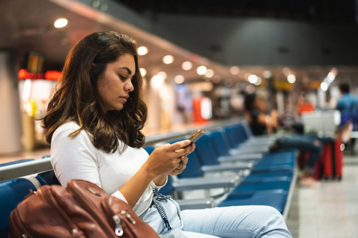 woman sitting in airport waiting to board flight