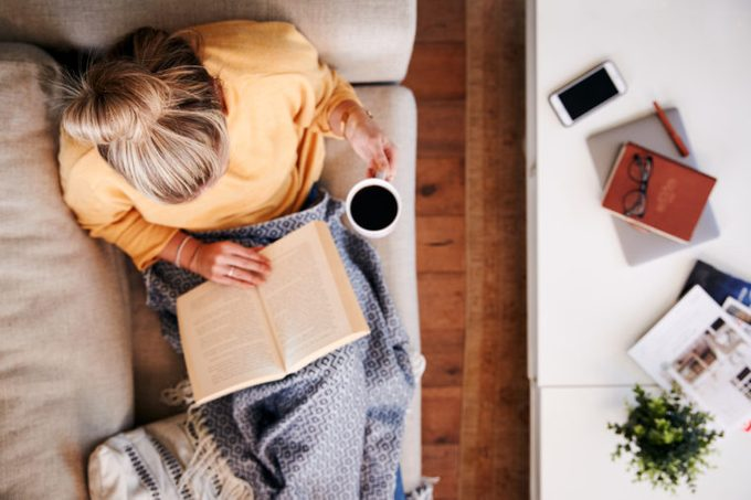 woman at home sitting on couch reading a book and drinking coffee