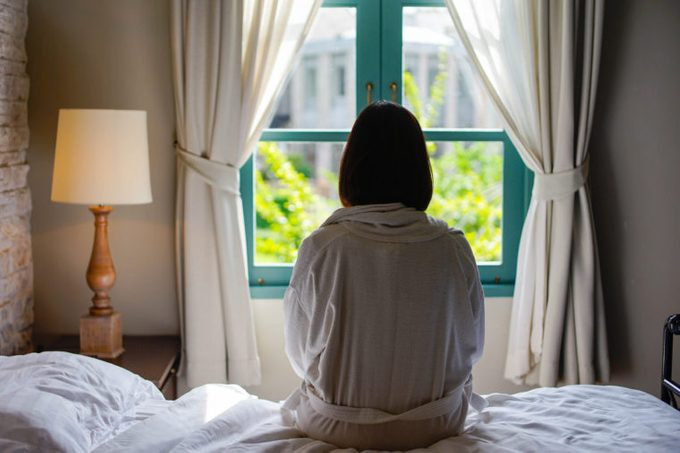 lone woman sitting on edge of bed