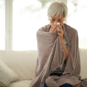 woman blowing her nose at home sick