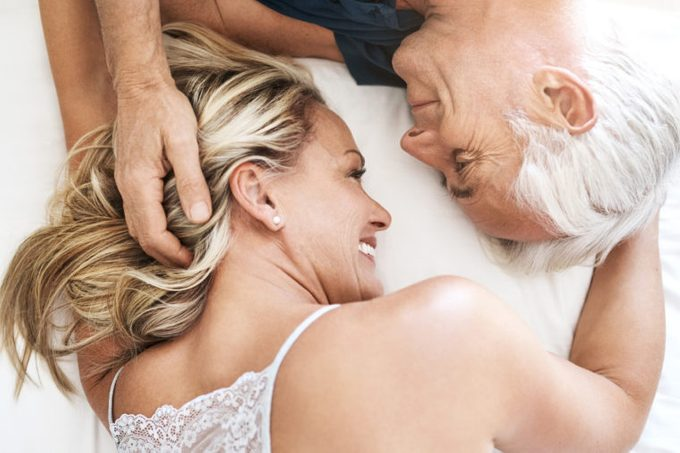 older couple laying down in bed together showing affection