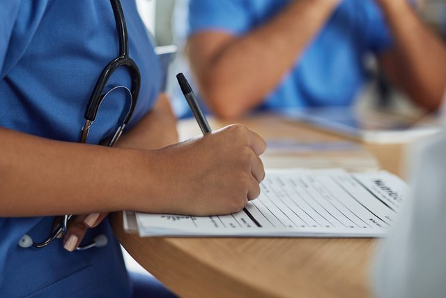 nurse writing on health papers