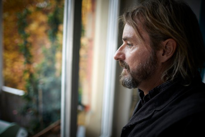 profile view of man looking out window