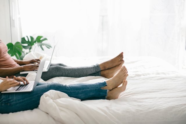 laying in bed using laptops