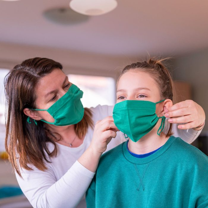 Mother wearing a homemade protective mask and putting one to her daughter DIY face mask
