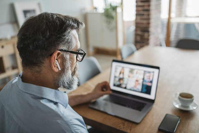 man on video conference call with coworkers working from home