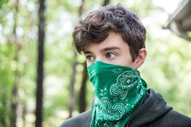 Teenage boy wearing bandana over face