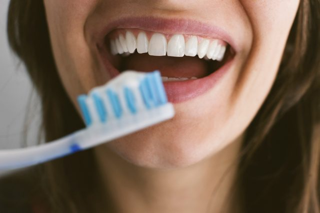 young woman brushing her teeth close up