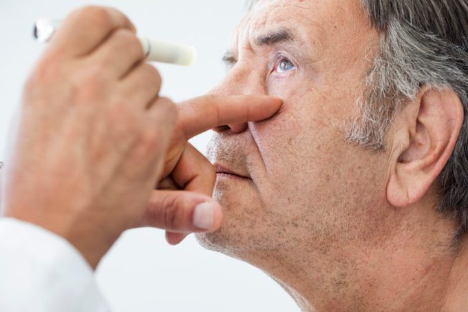 eye doctor examining elderly man's eyes