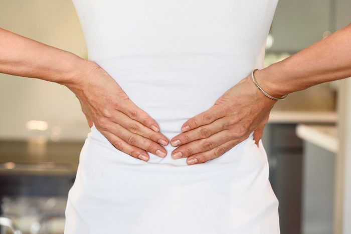 cropped rear shot of woman's hands on lower back
