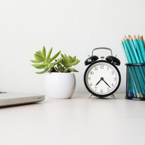 desk with laptop clock plant and pencils