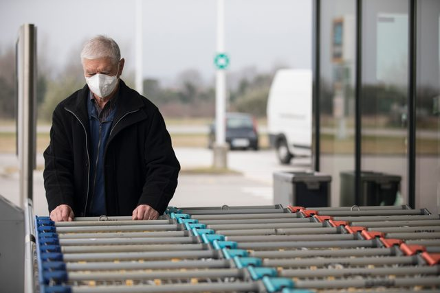 senior mad wearing face mask at grocery store to protect from coronavirus