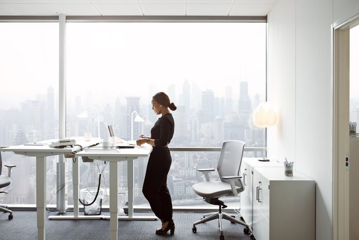 woman using standing desk at work