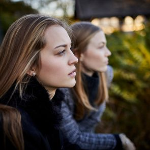 two young women leaning on railing looking at view