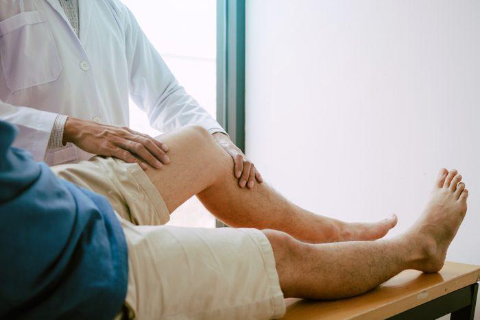 doctor examining patient's legs