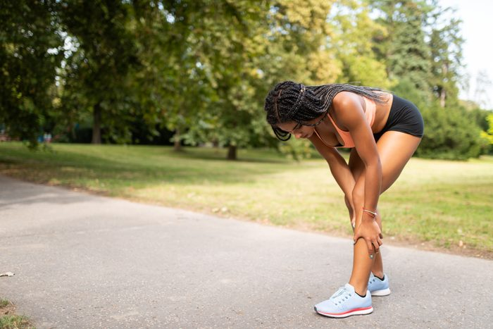 woman suffering from leg cramp muscle pain while exercising outside