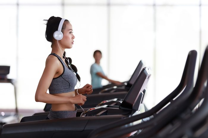 side view of woman walking on treadmill at the gym