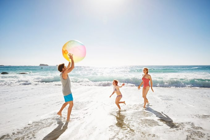 family playing with a beach ball on the beach