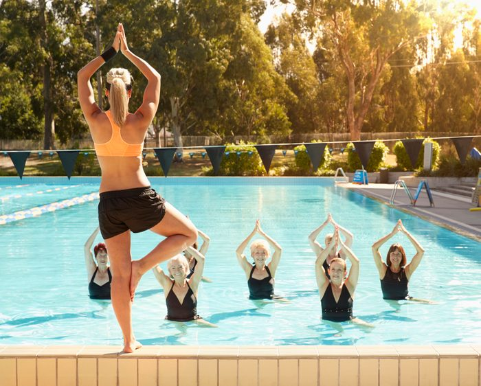 trainer leading older women in swimming pool aerobics fitness class