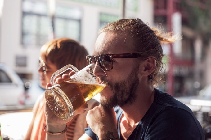 man drinking a beer at a restaurant