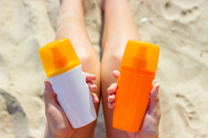 woman holding two different bottles of sunscreen on the beach