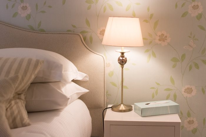 bedside table with lamp light on