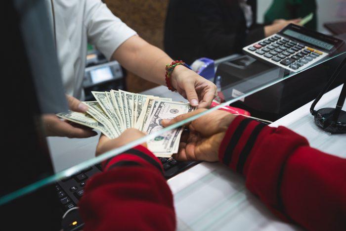 close up of banker giving customer cash