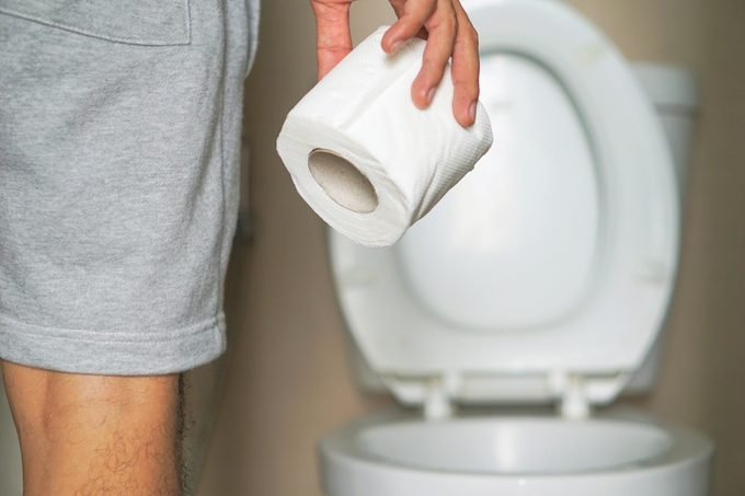 man holding roll of toilet paper
