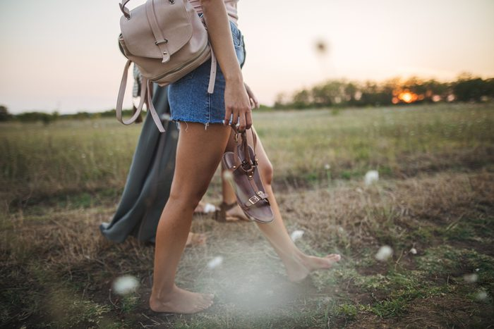 couple walking barefoot through field