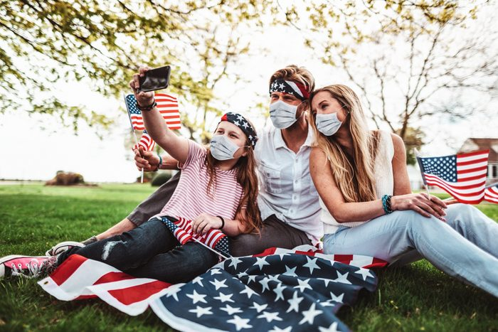 family celebrating fourth of july with face masks on to protect against coronavirus