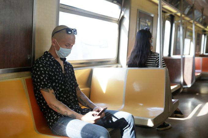two people sitting on the subway with face masks on