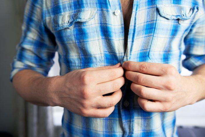 man buttoning shirt close up