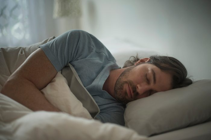 man laying asleep in bed