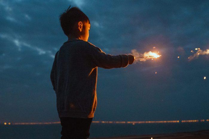 little boy holding sparkler
