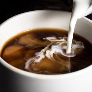 close up of milk being poured into a cup of coffee